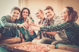 group of young multi ethnic friends with pizza and bottles of group of young multi ethnic friends with pizza and bottles of drink celebrating in home interior osmosis theme
