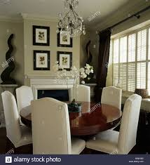 circular dining room tall back cream upholstered chairs and circular antique table in