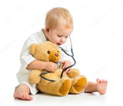 adorable child with clothes of doctor and teddy white