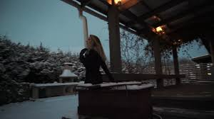 blonde woman in black clothes walk out suburban house to snow