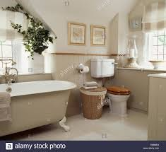 clawfoot bath in neutral bathroom with dado panelling and wicker