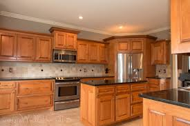 maple cabinets with black island what color granite goes with cherry cabinets white island black