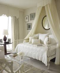 white stained wooden canopy bed frame with white bed linen and