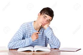 Picture Of Student Sitting At Desk Young Student Sitting On Desk And Learns For His Exams He Looks