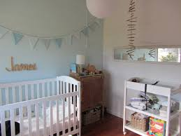 white wooden baby crib with brown wooden chest of drawer also