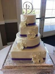 white wedding cake with deep purple satin ribbon bouquet wedding