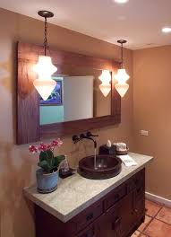 bathroom with round copper vessel sink and hanging pendants