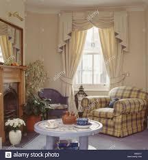 swagged and tailed cream curtains in neutral living room with