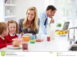 family having breakfast in kitchen before and work stock