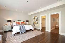 contemporary master bedroom with hardwood floors by studio d
