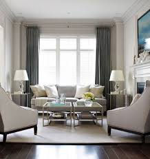 elegant living room with light grey sofa and arm chairs with