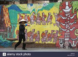woman walking past hanoi ceramic mosaic mural near old quarter of stock photo woman walking past hanoi ceramic mosaic mural near old quarter of hanoi vietnam southeast asia