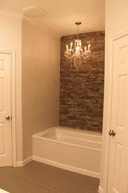 my tub with faux stone wall accent wall and chandelier bathroom