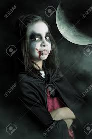 with face paint and halloween vampire costume in a dark