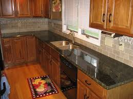 kitchen backsplash with black countertops and oak cabinets