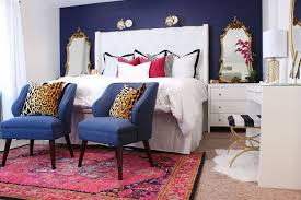 stylish bedroom with deep purple wall accent and ornate mirror