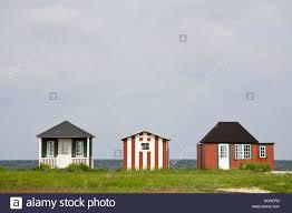 three individual three colourful tiny beach houses typically