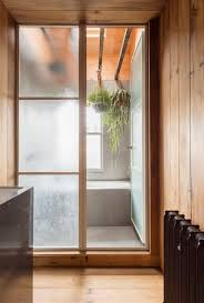 a japanese style two room bath filled with hanging plants crittal steel framed glass doors in architect simon astridge s own london bathroom nicholas worley