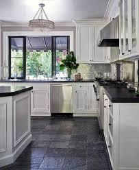 white kitchen cabinets black tile floor white cabinets countertop textural backsplash