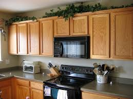 What To Put Above Kitchen Cabinets by Decorate Above Kitchen Cabinets Simple Varnished Mahogany Wood