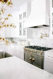 stunning white transitional kitchen with brass chandeliers