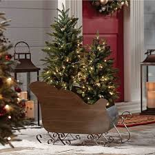 member s topiary in sleigh green tree with brown sleigh