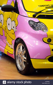 smart car pink smart car painted with simpsons cartoon characters stock photo