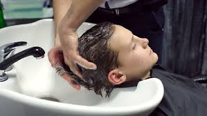 pretty verry young boys washing hairs close up of hairdresser washing the hair of a young guy in a