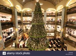 a giant christmas tree hangs from the ceiling of a department