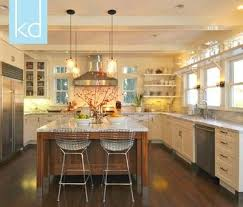 white kitchen wood island white cabinets marble counters wood island windows flankin
