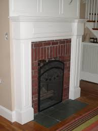interior black wooden carving fireplace with white tile surround