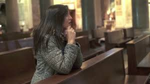 young woman kneeling and praying in church stock video footage