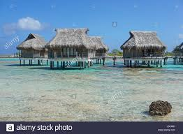 tropical lagoon and overwater bungalows with thatched roof atoll