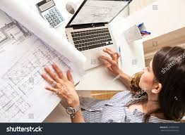 female architect working home looking blueprints stock photo