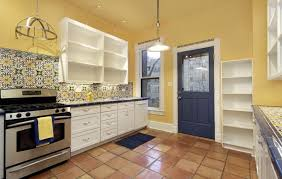 yellow wall color with terracotta floor for white cabinet paint