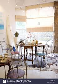 metal chairs at jacobean style table in coastal dining room with