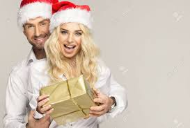 beautiful smiling couple in santa claus hats with presents stock