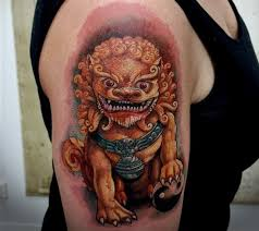 yellow colored foo dog tattoo on right shoulder