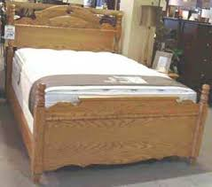 wooden bed frame with mattress and box spring displayed in a