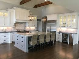 white inset cabinets with a dark wood floor decorative wood hood