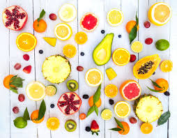 mix of colored fruits on white wooden background composition