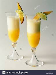 two champagne cocktails with fruit garnish on a white background