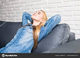 si e relax giovane donna felice che si siede sul divano e relax a casa sparare