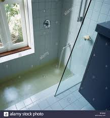 water pouring from chrome tap into sunken bath with glass shower