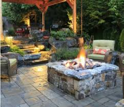 outdoor square backyard fire pit under plants with rattan chairs