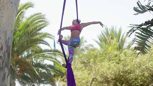acrobatic dancer working out on silk ribbons hanging