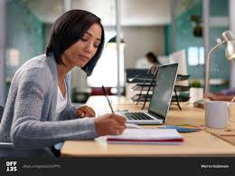 Student At Desk by Office Worker Writing Notes At Desk Stock Photo Offset