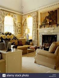 beige sofas and cream carpet in yellow country living room with