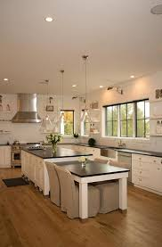 two glass cone shaped pendants hang over a white kitchen island