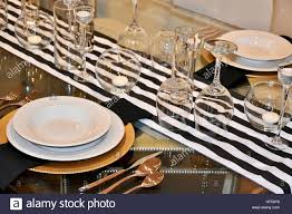 an elegant dinner set up prepared on a beautiful glass table for a